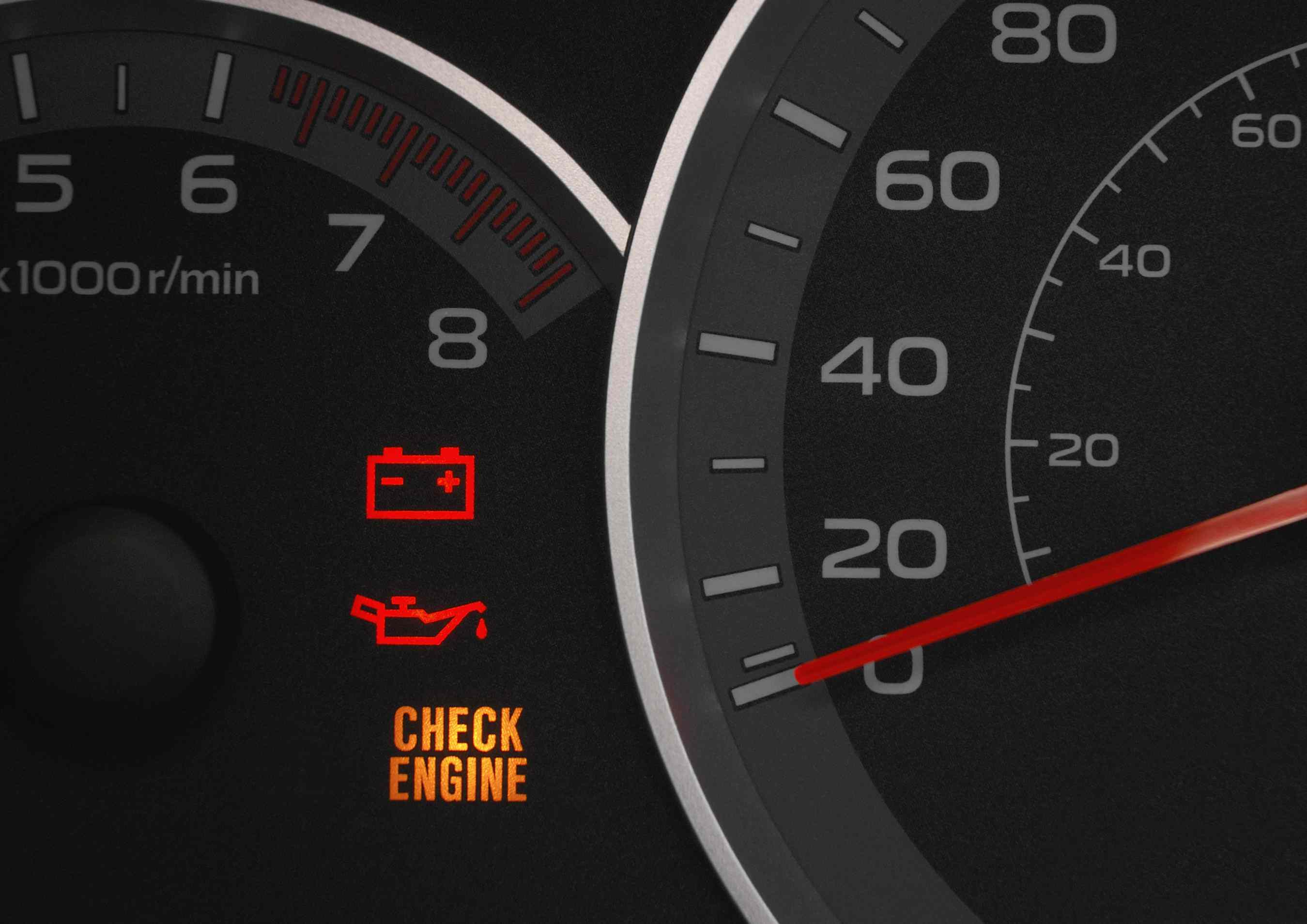 Close up on a cluster with the check engine warning light on indicating a  car failure