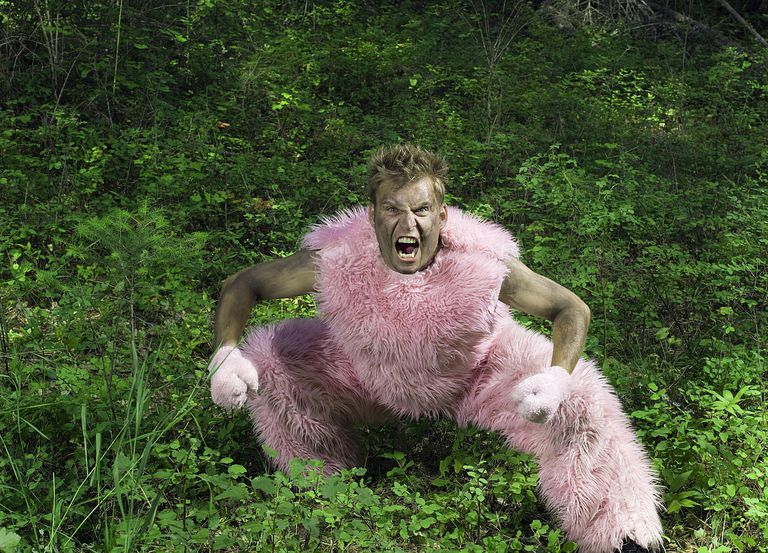 Yelling man wearing furry pink costume in underbrush.