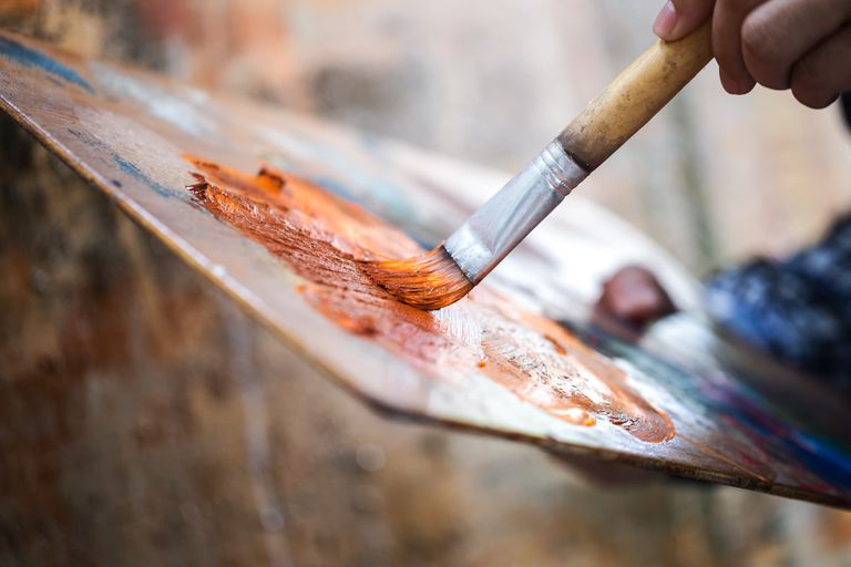 painter applying paint to a brush on a palette