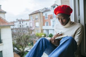 Young woman sitting on window reading