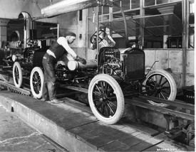 Picture of a worker attaching a gas tank on Ford's assembly line.