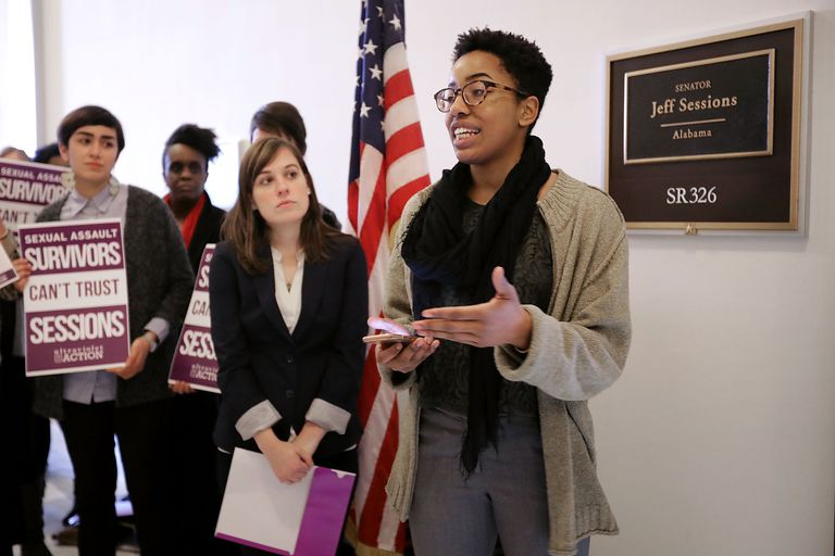"Survivors of sexual assault protest the nomination of Senator Jeff Sessions to the position of U.S. Attorney General because he claimed that President Donald Trump's self-described behavior of grabbing women ""by the pussy"" would not constitute sexual assault. Trump's words, actions, and Sessions' response to them are all evidence of rape culture."