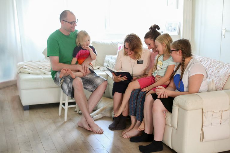 Missionaries teaching a family in a home