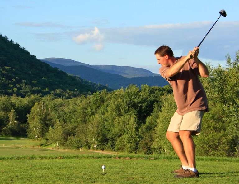 Golfer preparing to hit tee shot, hoping not to whiff