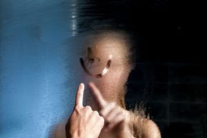 a man drawing a smiley face on a steamy mirror