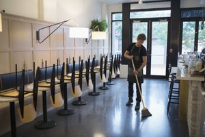 Male worker sweeping cafe with broom
