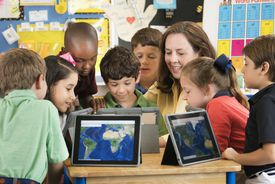 Teacher and students using digital tablets in classroom