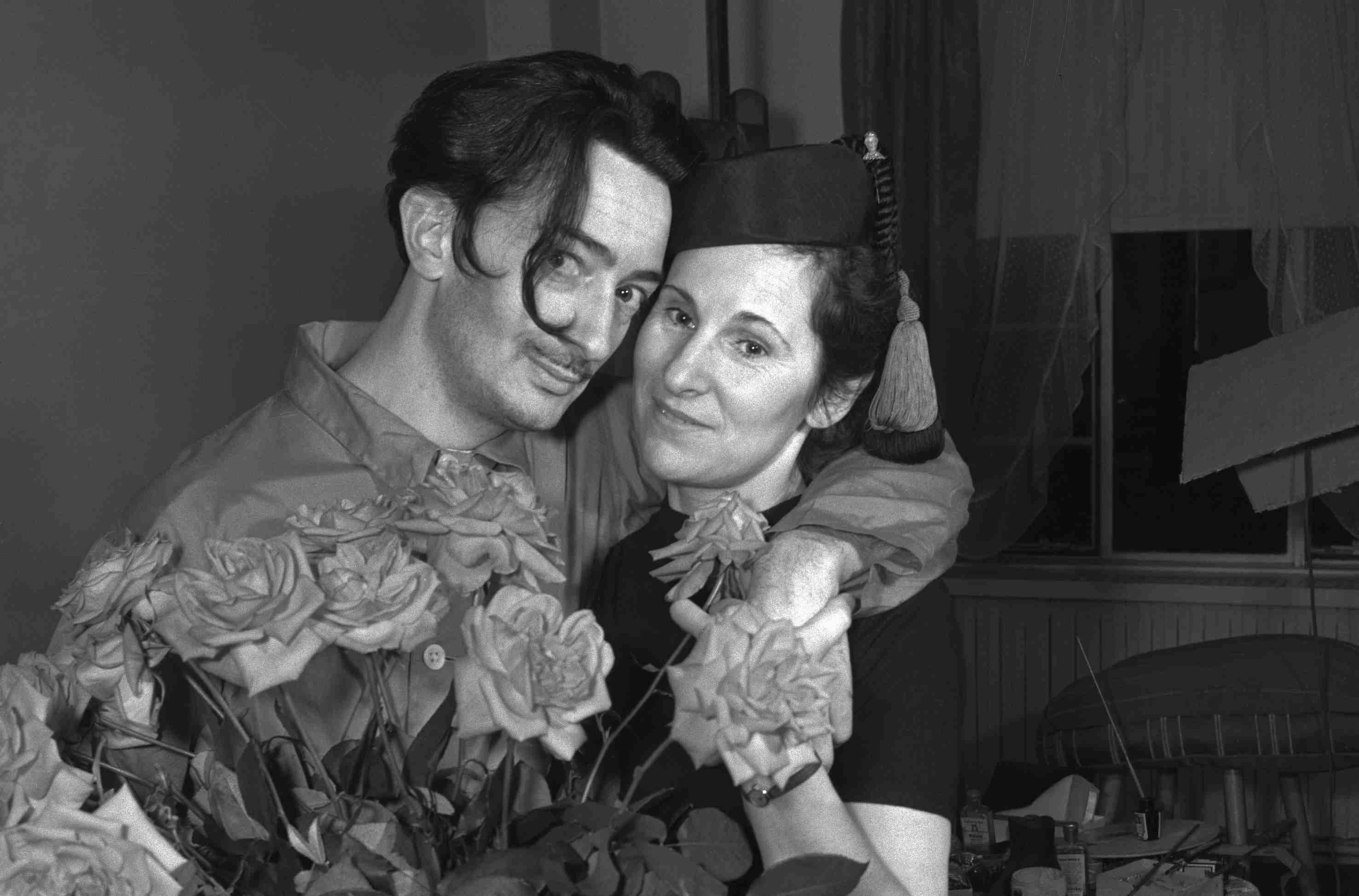Salvador Dalí and his wife embrace behind a bouquet of roses