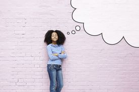 A girl thinking of topics beside a pink brink wall