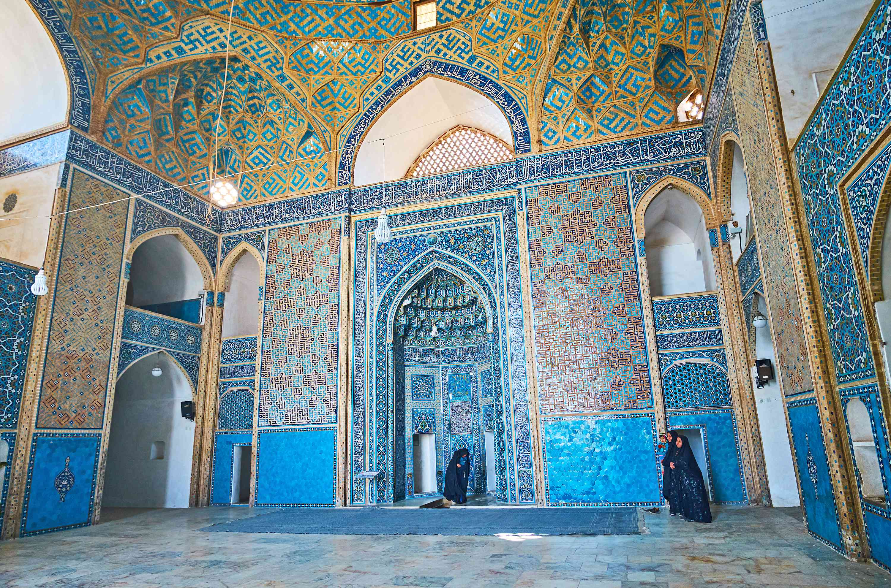 The dazzling Islamic patterns in the 14th century Jameh Mosque with a view on unique faience mihrab, Yazd, Iran.