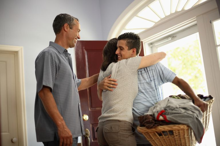 Son with a basket of laundry hugging his mother by the front door
