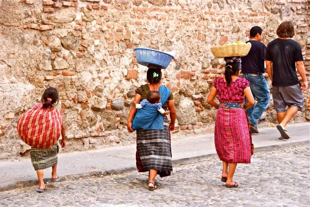Local women and tourists in Antigua, Guatemala.