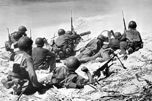 Marines take cover behind sand dunes in the opening phase of the invasion of Eniwetok