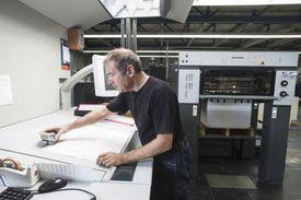 Worker preparing digital printing equipment in print workshop