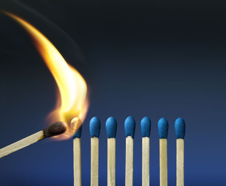 A lit match about light several other blue matches.