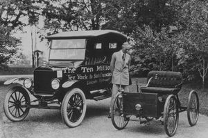 American motor vehicle industry pioneer Henry Ford (1863 - 1947) standing next to the first and the ten millionth Model-T Ford.