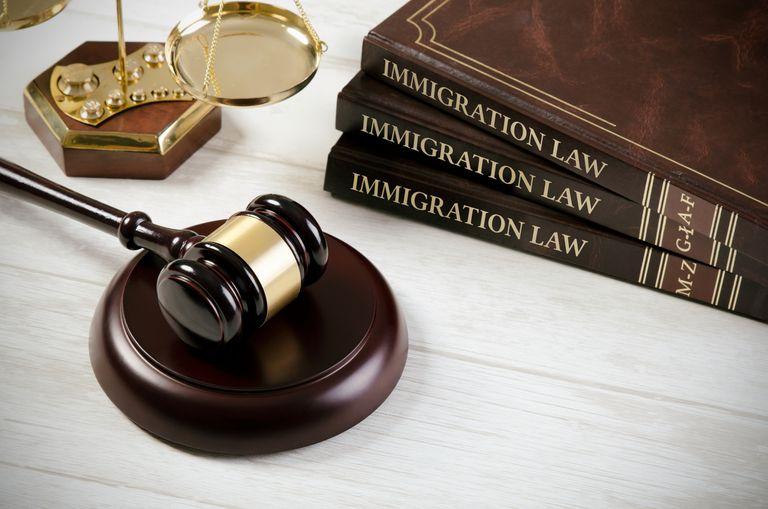 Libros de derecho inmigración, martillo juez y balanza Justicia.