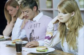 Young people with sickened faces looking at their burgers