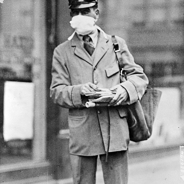 A picture of a letter carrier in New York wearing a mask for protection against the Spanish flu.