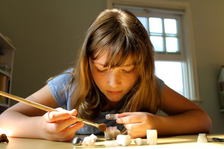 Young girl studying a collection of gems and minerals using a magnifying glass and brush to collect information while sitting at a desk. Childhood. Science.