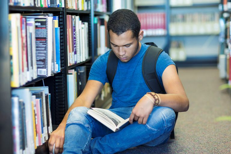 Male student sitting on floor in library reading a book