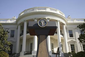 Presidential Seal on podium in front of The White House