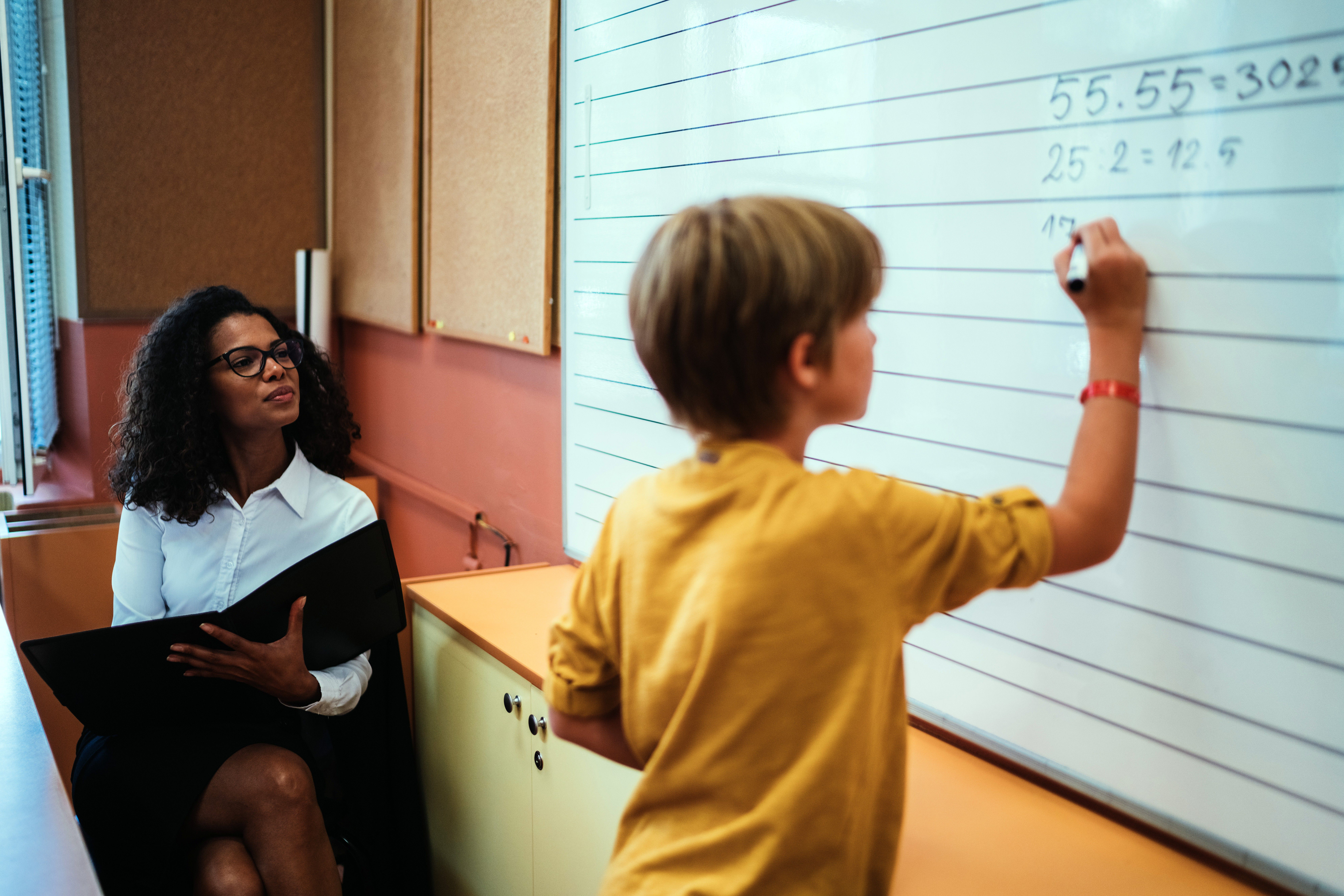 A boy does math problems on the whiteboard under the watchful eye of the teacher