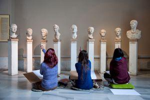 Students examining ancient sculptures.