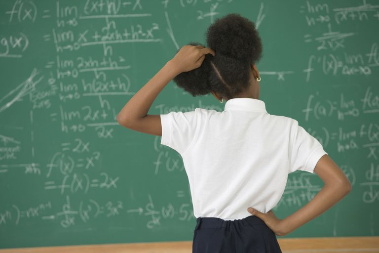 Girl looking at a chalkboard covered in math equations